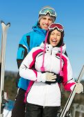 Half-length portrait of two embracing alps skiers with skis in hands
