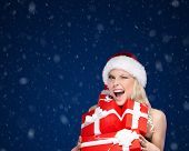 Pretty woman in Christmas cap holds a set of presents, winter background