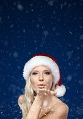 Beautiful woman in Christmas cap blows kiss, snow background