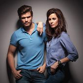 Fashion couple leaning on a grey wall while looking at the camera, the man is holding his hands in pockets, while the woman is leaning on him.