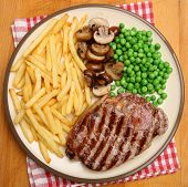 Chargrilled sirloin steak dinner with fries, mushrooms and peas.