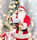 christmas, holidays and people concept - man in costume of santa claus with notepad over tree lights background