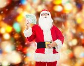 christmas, holidays, winning, currency and people concept - man in costume of santa claus with euro money over red lights background