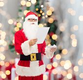 christmas, holidays and people concept - man in costume of santa claus reading letter over tree lights background