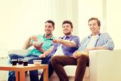 friendship, technology and home concept - smiling male friends with remote control and junk food at home