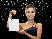 advertisement, winter holidays, christmas and sale concept - smiling woman with white blank shopping bag over black background over black snowy background