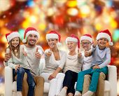 family, happiness, generation, holidays and people concept - happy family in santa helper hats sitting on couch and showing thumbs up gesture over red lights background