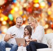 family, holidays, shopping, technology and people - smiling family with tablet pc computer and credit card over red lights background