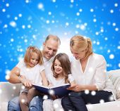 family, childhood, christmas holidays and people - smiling mother, father and little girls reading book over blue snowy background