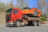Red Volvo F12 Intercooler Hauls A Hitachi Zaxis Excavator