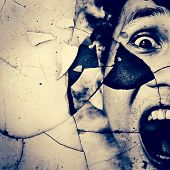 stock photo of possess  - Screaming Man Face On Shattered Grunge Wall Background - JPG