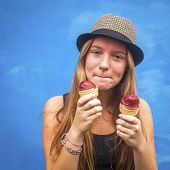 Portrait of teengirl with ice cream, blue wall background (Instagram style series)
