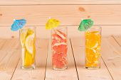 Close up of sliced fruits in collins glasses.