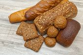 Fresh Bread Of Different Varieties On Wooden Background