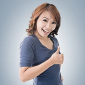 Smiling Asian woman give you a thumb up gesture.