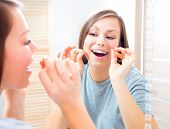 Beauty teenage girl flossing her teeth at home. Pretty young woman using an interdental brush smiling at the mirror enjoying beautiful white teeth. Healthcare of mouth and dental floss. Dental hygiene