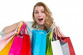 Overwhelmed young woman with shopping bags on white background