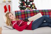 Day dreaming young woman lying on couch at home in the living room