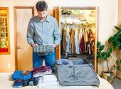 A man is packing his suitcase for a trip