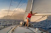 pic of blinders  - Woman sailor stays at deck of sailing yacht going at full sails to sunset - JPG