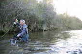 Fly fisherman catching trout in landing net