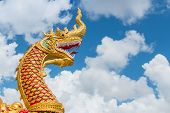The Golden Great Naga Statue With White Cloud And Blue Sky Backgroud.