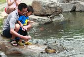 Daddy and his son are feeding fish in park