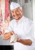 Portrait of happy mature butcher offering chicken pieces covered with flour in shop