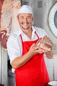 Portrait of confident male butcher showing meat piece while standing in butchery