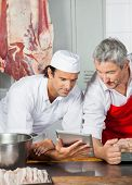 Multiethnic male butchers using tablet computer while leaning on counter in butchery