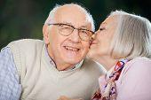 Senior woman kissing on man's cheek at nursing home