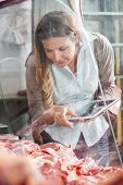 Mature woman holding digital tablet while choosing meat at butchery