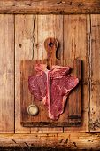 Raw Fresh Meat T-bone Steak And Weight On Cutting Board On Wooden Background