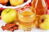 Apple cider with cinnamon sticks and fresh apples on cutting board, on wooden background
