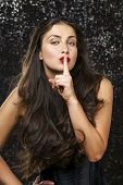 Young beautiful brunette woman has put forefinger to lips as sign of silence