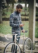 Hipster Man With A Fixie Bike And Smartphone