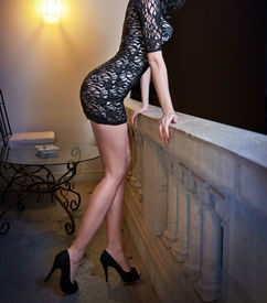stock photo of tight dress  - Fashionable perfect body young woman in little black dress posing on a ledge - JPG
