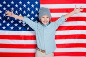 picture of little boys only  - Little boy in eyewear keeping arms raised and smiling while standing against American flag - JPG