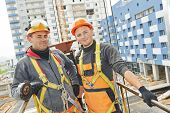 image of real-estate-team  - Team of smiling facade builders workers in protective uniform at construction building site - JPG