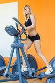 stock photo of elliptical  - Young sports woman doing exercises on an elliptical trainer in the gym - JPG