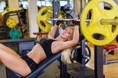 stock photo of bench  - Sports young woman doing exercises with barbell on bench in the gym - JPG