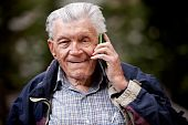 stock photo of senior-citizen  - A portrait of a senior using a cell phone outdoors - JPG