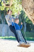 picture of swing  - happy mother and her son having fun swinging in the park mother - JPG