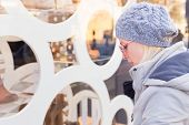 stock photo of boutique  - Casualy winter dressed lady window shopping in front of sinfully expensive boutique store dispaly window. Customer woman in shopping street, looking at window, outdoor. ** Note: Soft Focus at 100%, best at smaller sizes - JPG