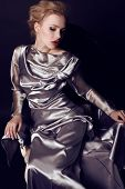 stock photo of silver-hair  - fashion studio photo of gorgeous woman with blond hair and bright makeup wearing luxurious silver dress - JPG
