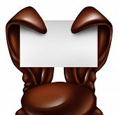 stock photo of ear  - Easter chocolate rabbit sign as sweet confectionary ears holding a blank banner card as a fun spring symbol of holiday celebration as an advertising message on a white background - JPG