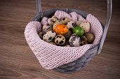 picture of quail egg  - Quail eggs in a basket and one orange green egg with pink knit on wooden background - JPG