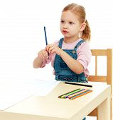 foto of montessori school  - Little girl draws pencils sitting at the table - JPG