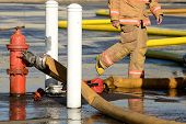 stock photo of firefighter  - Firefighters at the fire hydrant while using large volume appliance water delivery master streams  - JPG