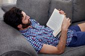 foto of lounge room  - man relaxing on sofa couch reading literature novel story book at home living room lounge - JPG